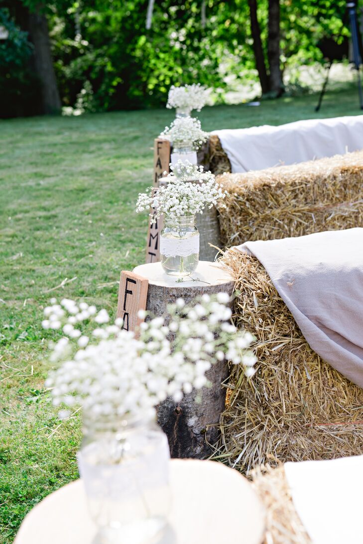 To give the ceremony a rustic feel, haystacks were used as the ceremony pews and the aisles were lined with mason jar floral arrangements placed on top of logs.