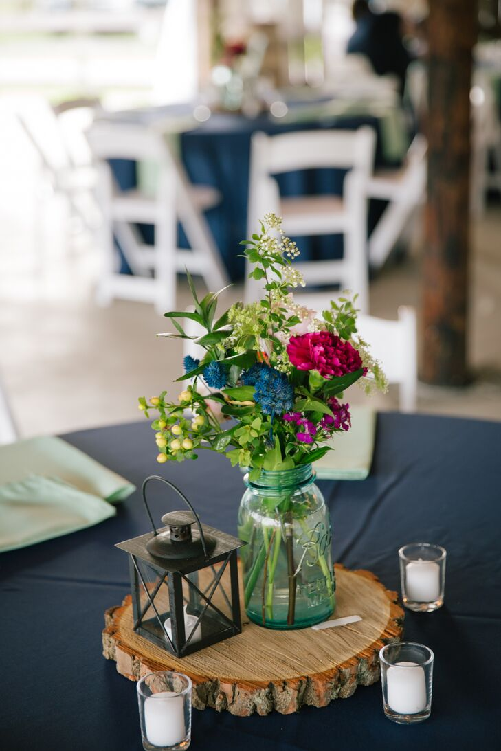 The dining table centerpieces included hand-cut wooden slabs with vintage mason jars filled with colorful fresh flowers. Small lanterns and candles added a romantic touch.