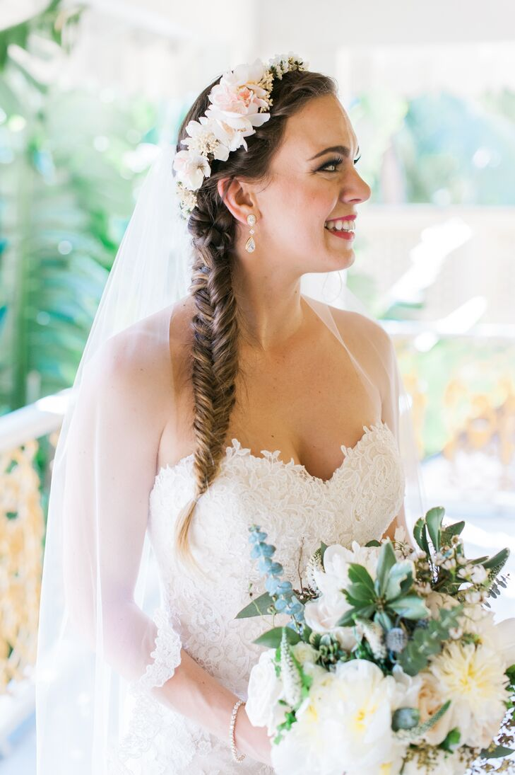 """""""I wanted to be a comfortable bride and didn't want to worry about my hair going crazy in the Florida heat, so I wore my hair in a loose twisting fishtail braid, topped with a flower crown that my mom and Lala made for me,"""" Ashleigh says. The look went perfectly with her Spanish lace, sweetheart dress."""