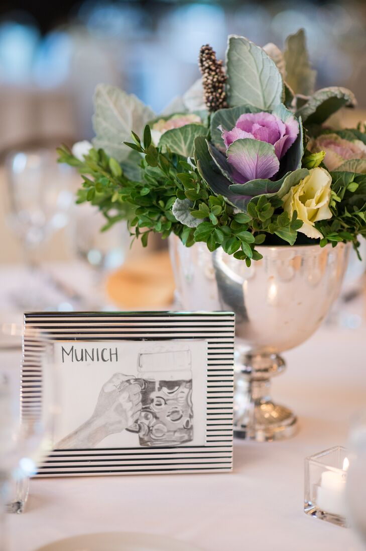Silver urn centerpieces carried lush green arrangements with delicate pink and yellow roses. Marguerite's sister sketched the framed table numbers, which indicated various places that were meaningful to the bride and groom.