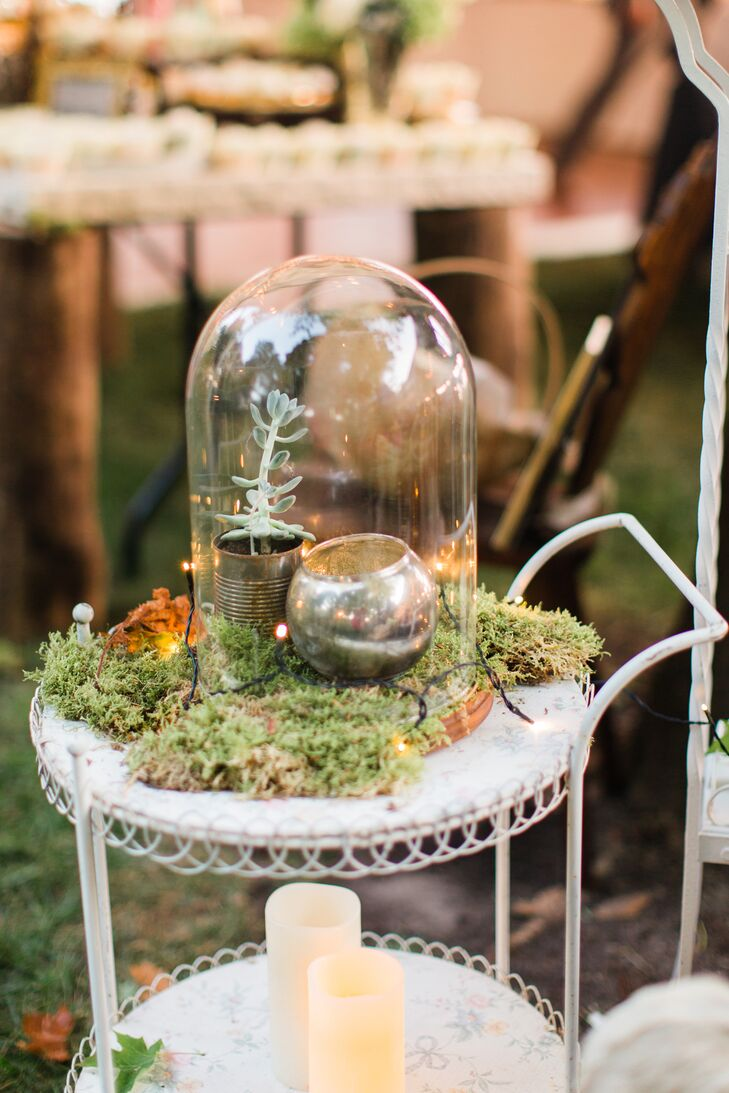 Mercury-glass votives and live moss were displayed in terrariums placed on top of vintage white carts.