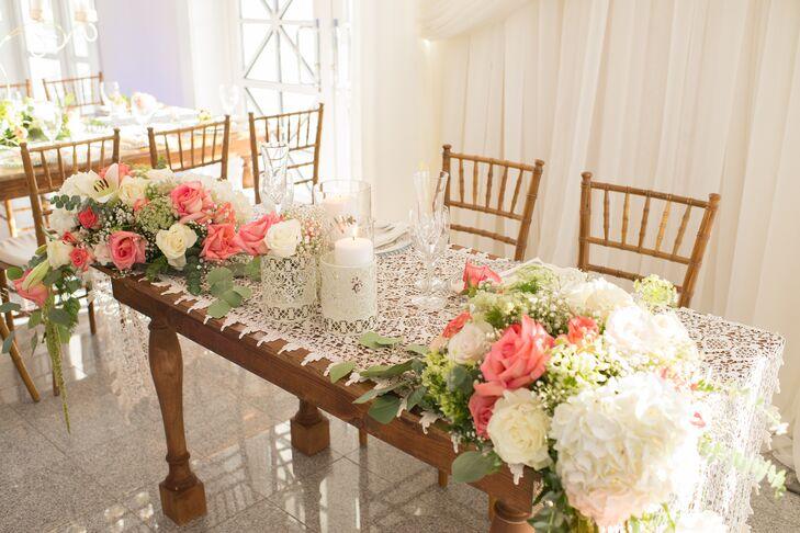 Natalie and Chris's sweetheart table had a lace runner that channeled their vintage decor inspiration. Two arrangements of white hydrangeas, baby's breath and ivory and coral roses with pops of greenery draped over the table ends.