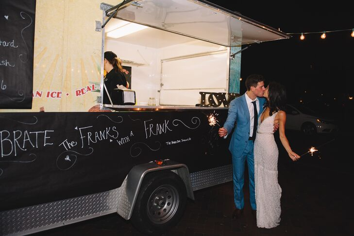 "At the end of the evening, Molly surprised Michael with a food truck. ""One of my favorite details was my surprise for Michael. He is really obsessed with late-night food. He always mentioned how he wanted late-night food served at the wedding, and I would just tell him we had enough food,"" Molly says. ""When we made our sparkler exit at the end of the night, sitting at the end was a hot dog truck that read 'Celebrate the Franks with a frank!' """