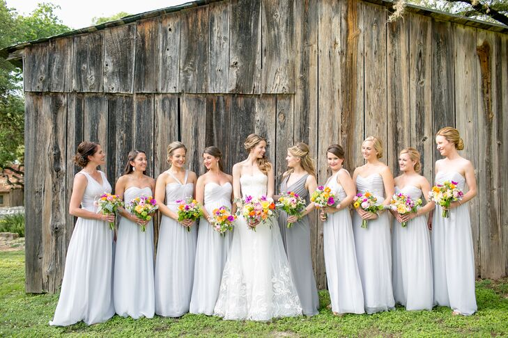 Bridesmaids donned floor-length dove-gray gowns to complement the romantic style of Lauren's strapless Monique Lhuillier gown.
