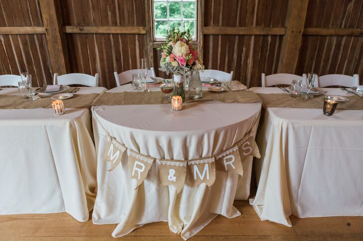 Guests sat on white folding chairs at tables topped with neutral linens and burlap runners. A rustic, pennant banner made from burlap adorned the front of the couple's sweetheart table.
