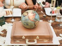 Traveling couple's groom's cake with globe, suitcase and airplace