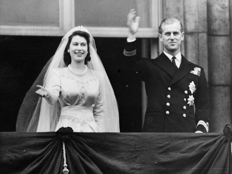 Queen Elizabeth and Prince Phillip waving from balcony of Buckingham Palace on wedding day