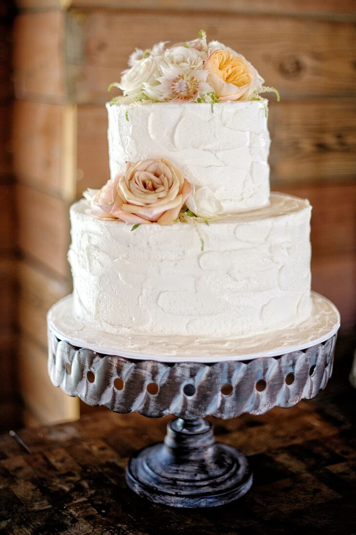 The two-tier wedding cake was covered in white buttercream frosting, and was accented with neutral-color flowers on the side and top. The cake was positioned on top of a silver stand for guests to admire and enjoy.