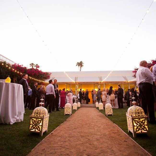 White lanterns lit the path to the tented area for the reception.