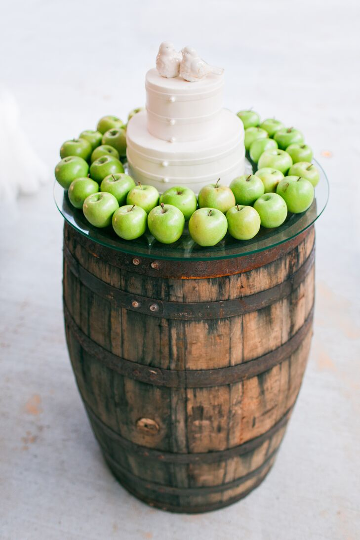 This vintage-inspired wedding cake sat atop a distressed wooden barrel on a round glass slab. Madison placed green apples around the confection to pull in some color.