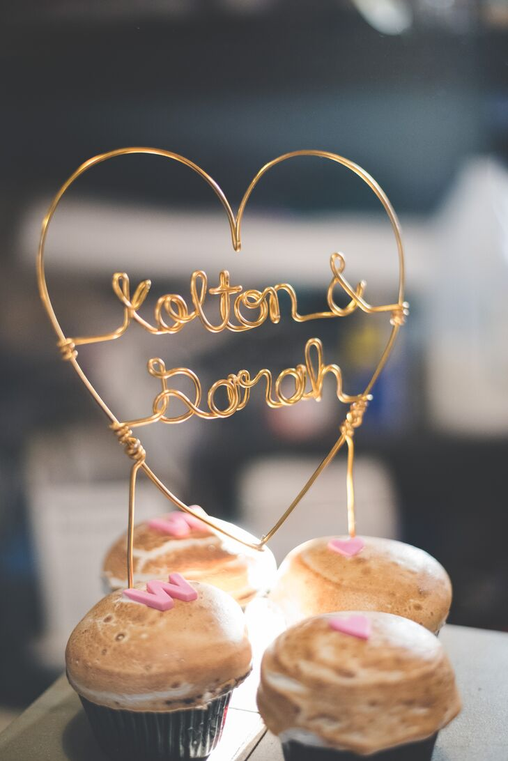 """S'mores cupcakes were browned on top and displayed on a stand at the reception for dessert. On top of the assortment was a wire sign that spelled out """"Kolton & Sarah."""""""