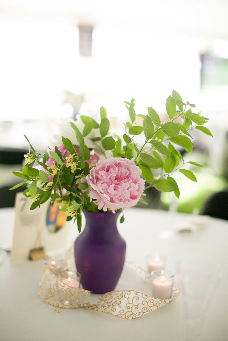 Pink peonies were used in the bridal and bridal-party bouquets and as part of the reception centerpieces. Vases were also painted a plum color to match other details like the bridesmaid dresses and DIY picture display.