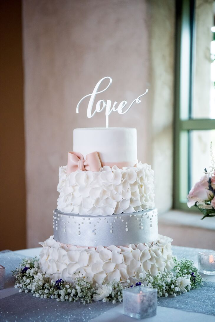 The multilayer cake included a tier of lemon, a tier of raspberry, a tier of Funfetti and a gluten- free Funfetti top. The design was selected from Showboy's gallery, with the color of the bow customized to match the ribbon on Anna's gown.