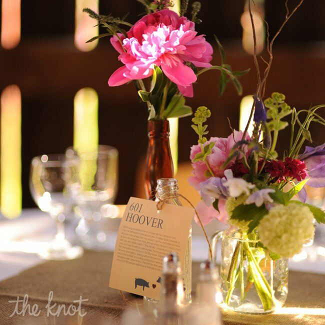 Peonies, sweet Williams and lisianthus filled an eclectic mix of glass bottles. For a personal touch, each table was named after a different place the couple had lived.