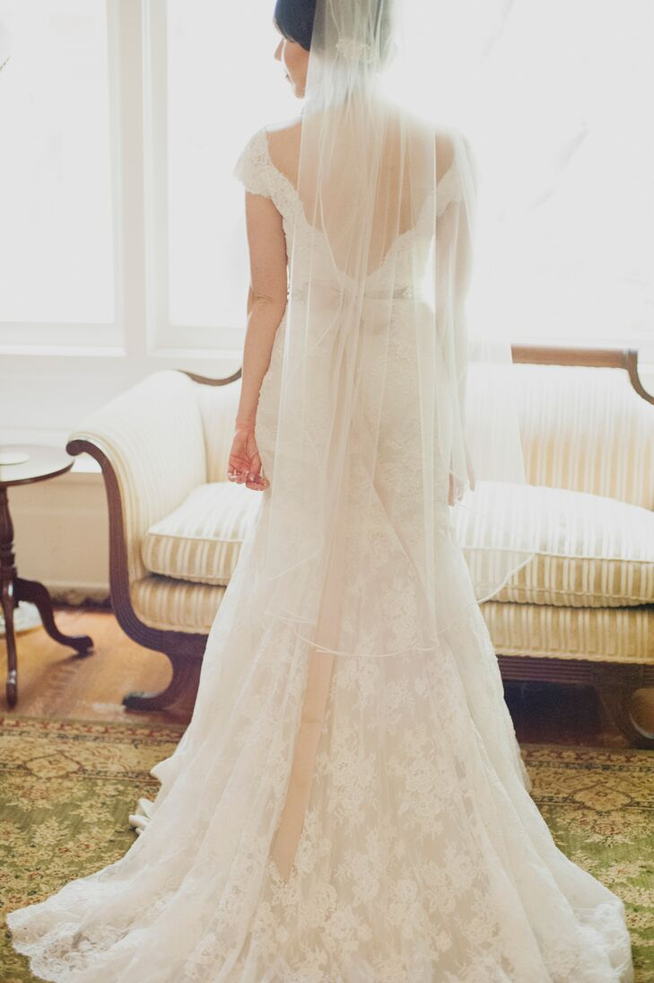 Katy wore an Allure Bridals dress that combined a vintage and romantic look. The entire gown covered in lace had a deep V-neck back with buttons going down the middle. Her fingertip-length veil added an elegant touch.