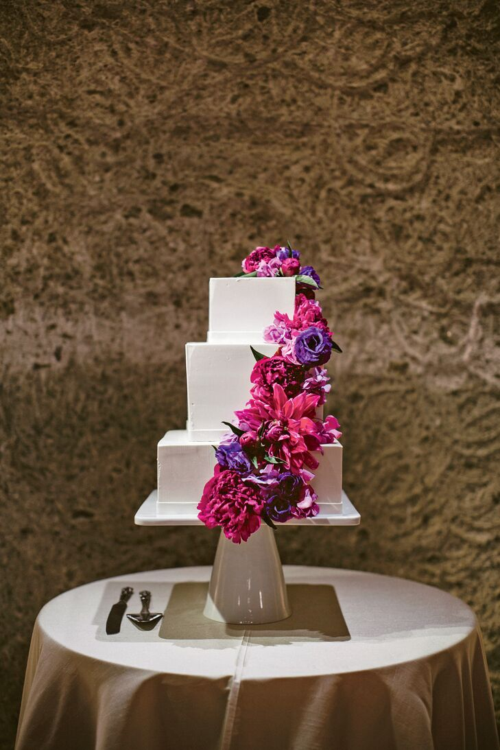 A cascade of purple and magenta flowers accented the couple's modern buttercream cake.