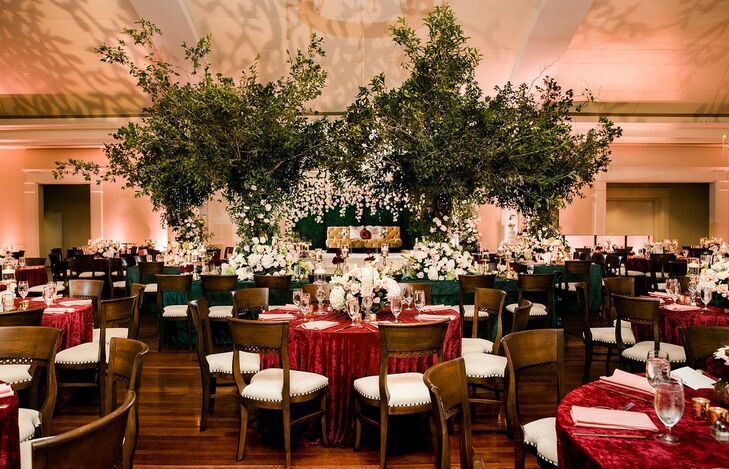 Elegant Indoor Reception with Red Tablecloths and Tall Trees