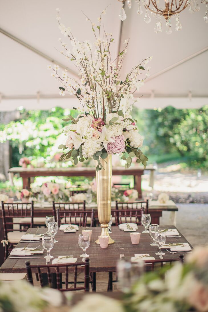 The reception was decorated with rustic wooden farm tables in different heights. The tallest tables were topped with gold-vase flower arrangements to draw the eye toward the gorgeous gold and crystal chandeliers. The centerpieces included lilies, roses, hydrangeas and branches for an English garden aura.