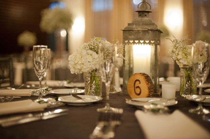 Centerpieces at the reception included silver candlelit lanterns beside small flower arrangements of white hydrangeas and baby's breath. There were also taller centerpieces made up of baby's breath. Table numbers were carved into small tree rings.