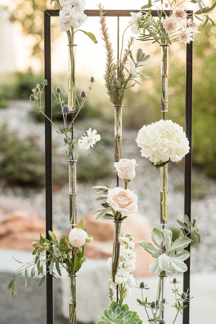 Maintaining focus on Utah's natural beauty, the only decor at the outdoor ceremony was a pair of rectangular wire frames, which held about a dozen test tubes stocked with a variety of succulents and flowers.
