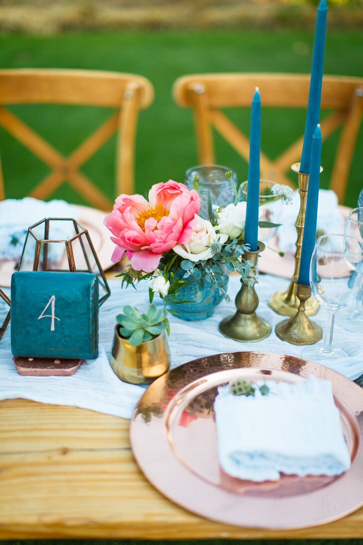 "Wooden farm tables were topped with light blue runners, rose gold chargers, blue goblets, taper candles, succulents, blooms and terrariums. ""The blue vintage water goblets and blue taper candles were just some of my favorite parts of the table decor,"" Taylor says. ""They added that extra pop of color I was looking for."""