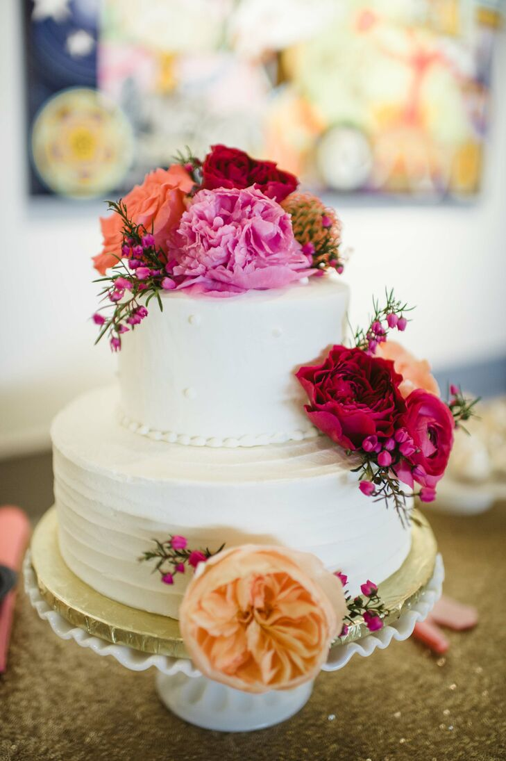 Erin and Matt's cake had two tiers and was frosted with buttercream. Colorful peonies, garden roses, spray roses, pincushion proteas and ranunculus added a whimsical touch.