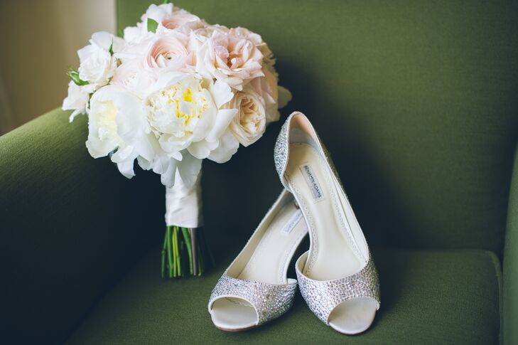 "Pamela wanted to make sure her wedding day look included a ""bling"" factor. So, she sported a stand-out pair of Swarovski crystal-accented heels by Benjamin Adams. For her bouquet, however, she kept things subtle and romantic. Fleurescent filled its white satin wrap with white peonies, blush ranunculus as well as pink and ivory roses."