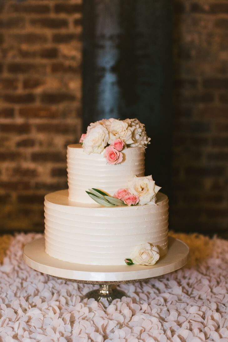 Even the couple's wedding cake got in on the garden theme, with the petite two-tier confection featuring combed ivory buttercream covered in clusters of fresh ivory and pink florals. The cake was displayed in the barrel room where the postdinner fun took place, with a textured petal-inspired tablecloth drawing the eye to the center of the room.