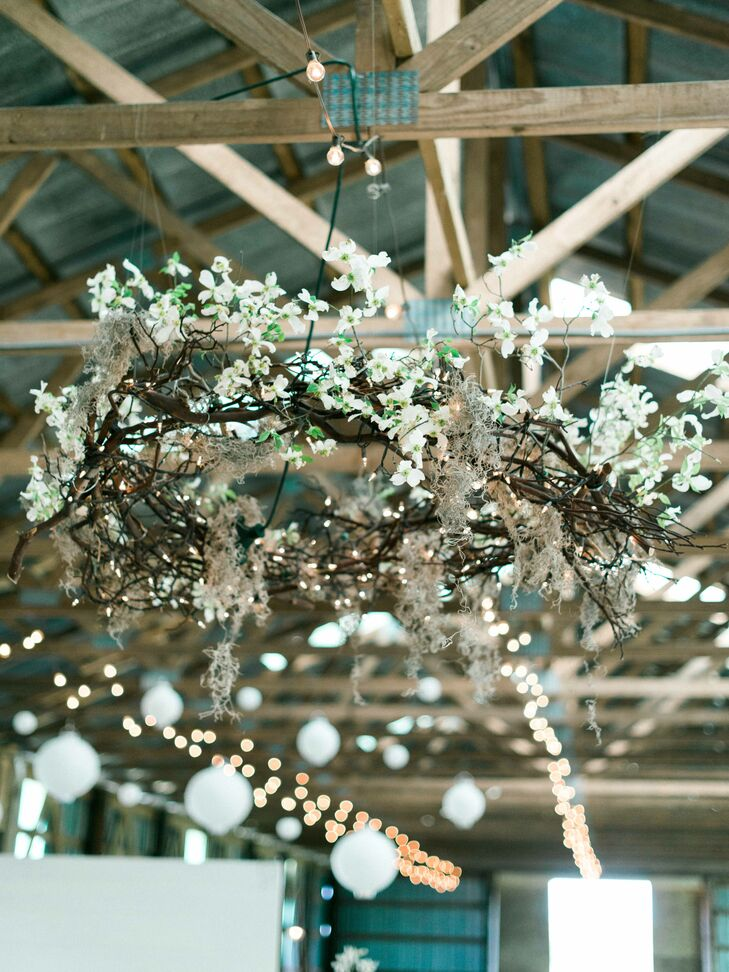 Hanging from the rustic exposed beams of the old barn was a beautiful handmade chandelier of fresh flowers wrapped around a halo of twigs and string lights. This creative use of greenery softened the ambience of the rustic venue and provided overhead lighting.