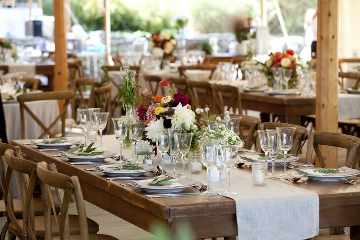 Mason jars, jam jars and vintage bottles held low and eclectic centerpieces. Long wooden farm tables with linen runners finished the look.