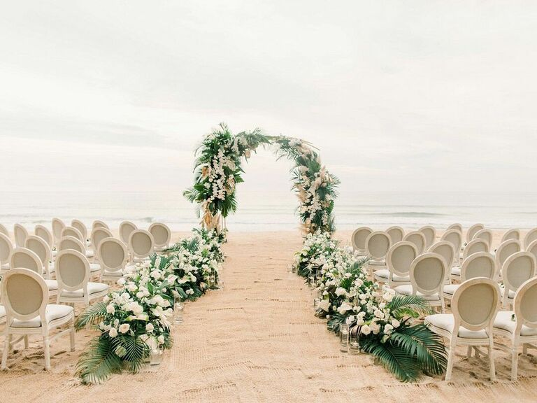 Flowers lining aisle and ceremony arch at summer beach wedding