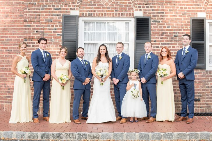 Their wedding party looks put a soft, modern twist on the couple's nautical theme. Each bridesmaid wore a floor-length pale yellow dress by Bari Jay with her favorite neckline and hairstyle. Their white-and-blue-striped bouquet wraps hinted at the day's motif. The couple's groomsmen, however, took a more literal approach. Each man donned blue and white apparel, including a blue Calvin Klein suit, white monogramed shirt and matching blue tie.