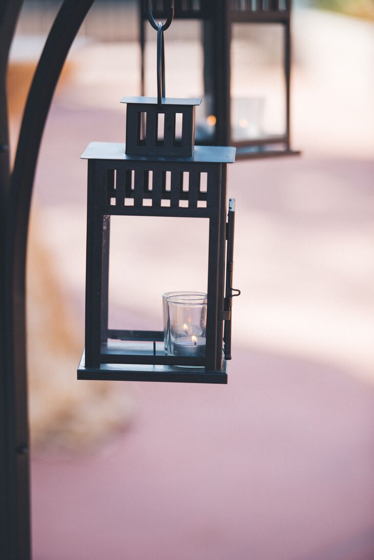 Hanging black lanterns with a single candle decorated the aisle at the ceremony.