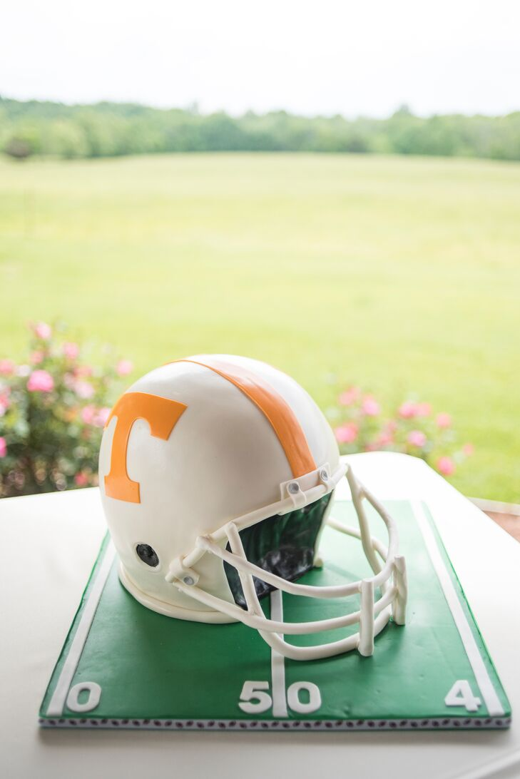 This Tennessee Volunteers football helmet groom's cake says it all. Tis So Sweet Cakes spared no detail, from the helmet to the football field details on the base.