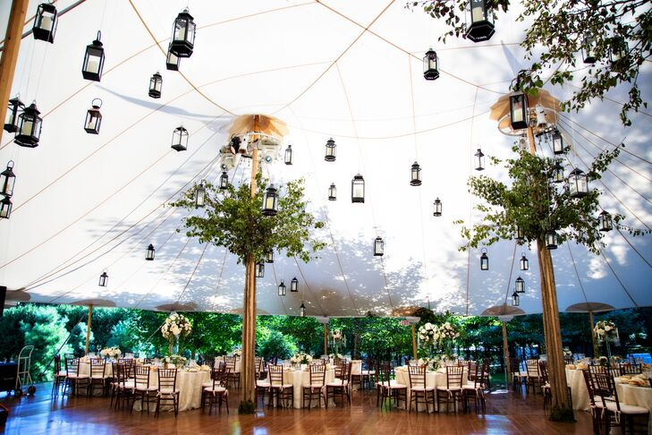 "With a ""Midsummer Night's Dream""-inspired theme in mind, Simin and Nicholas knew whimsical touches were a must for their garden soiree. Advanced Lighting & Production Services more than delivered, illuminating the Sperry tent's vast ceiling with a network of twinkling carriage lanterns that were suspended to look like they were floating in the air."
