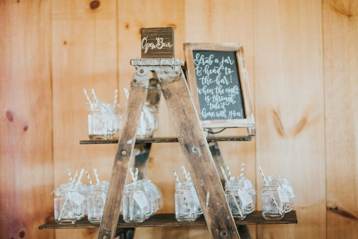Mason Jars with Paper Straws Displayed on Rustic Ladder