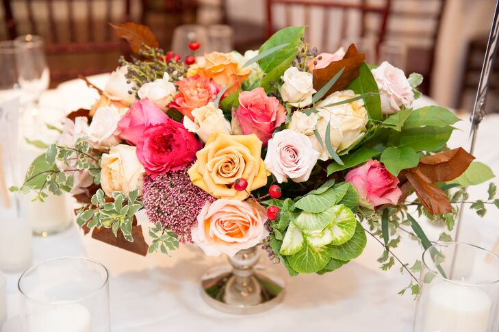 The dining tables at the reception were decorated with low, loose pedestal centerpieces with coral, peach and blush roses and greenery.
