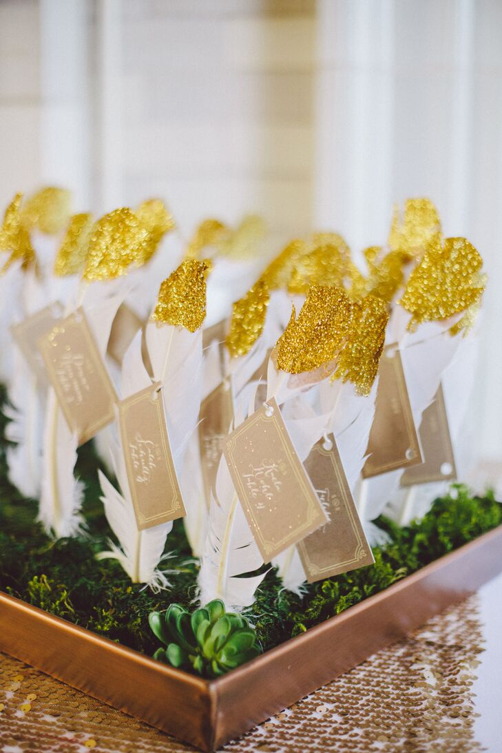 "The DIY escort cards were each tied to a gold glitter-dipped white feather stuck in floral foam boards covered in moss and succulents. ""It was one of my favorite things we made for the wedding!"" says the bride."