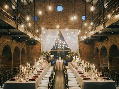 Rusing wedding reception venue with hanging bulb lights and tables with candles and flowers