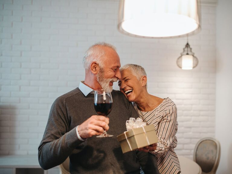 Older couple laughing and embracing with glass of wine and wrapped gift