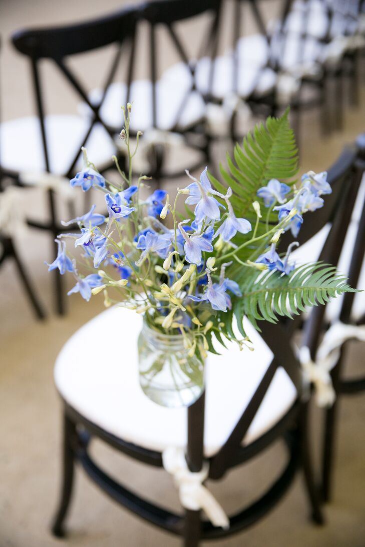 Simple glass bottle vases held arrangements of blue blossoms.