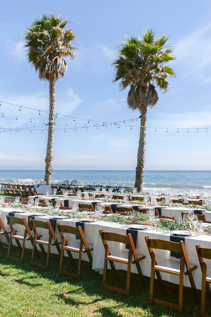 Classic Waterfront Dining Tables with Ivory Linens, Folding Chairs and String Lights