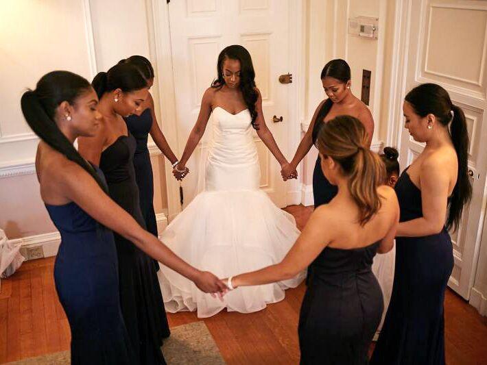 Bride and bridesmaids saying a prayer