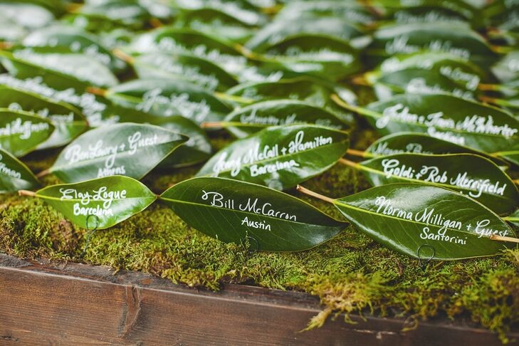Guests' names and table assignments were written with white ink on glossy green leaves.