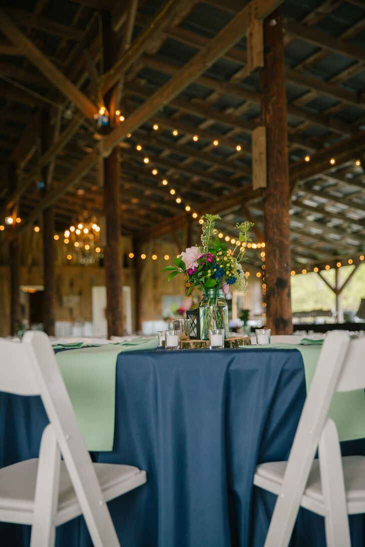 Navy dining tables with light green accents matched the rustic barn setting. White folding chairs added a classic contrast and Southern touch.