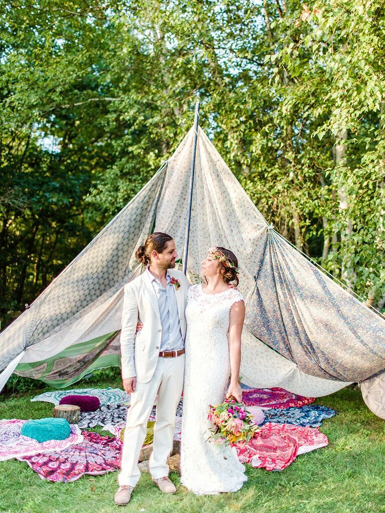 boho bride and groom in front of tent
