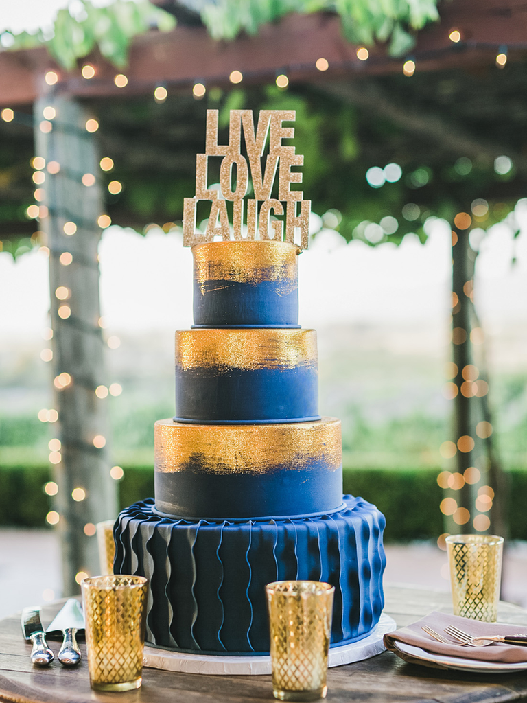 A navy fondant wedding cake with bright gold brushed tiers