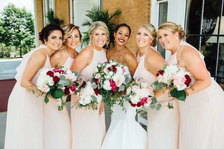 Channeling the romantic vibe of the secret garden-inspired affair, Jamila had her bridesmaids don blush chiffon gowns from Bella Bridesmaids in an A-line silhouette. A halter neckline gave the gowns a modern feel, while ruffled detailing along the back added the perfect punch of playfulness to their look.
