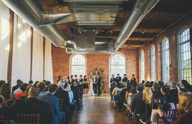 Laura and Blair decided to exchange vows at The Cotton Room in Durham, North Carolina, because they loved the aesthetic and history of the place, it was located within the Golden Belt of historic textile mills (think: giant windows, exposed brick and gorgeous hardwood floors) and it allowed them to have the ceremony and reception in the same place. Plus, the venue provided everything they needed from in-house catering to linens to lighting.