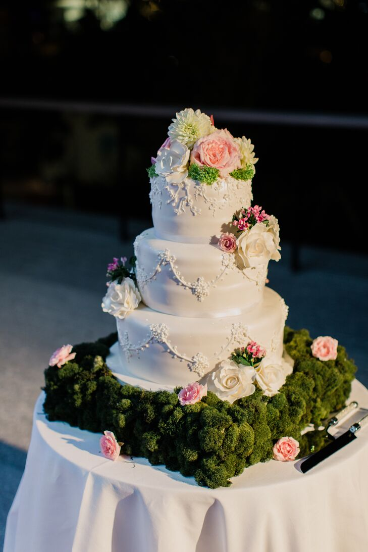 Talk about classic! The pros at Dominique's Couture Cakes made a tiered, garden-inspired cake covered in white piping and floral details. On top of that, every tier was accented with fresh pink roses, greenery, white roses, pink garden roses or white dahlias.